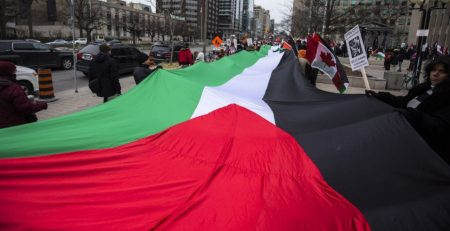 Protesters hold a giant Palestinian flag as they walk across University Avenue during a demonstration in Toronto, Canada, December 9, 2017. (Photo by Giordano Ciampini/Anadolu Agency/Getty Images)